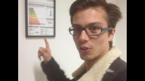 Foto de Hugo Roy señalando una imagen pegada en la pared donde aparecen las categorías energéticas de los electrodomésticos