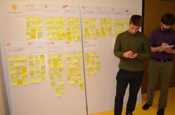 Fotografía de un panel donde, de una manera ordenada, se encuentran pegados una gran cantidad de pósit recogiendo ideas propuestas por los participantes.